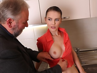 Katia shows off her erotic body in the kitchen in her pink and let slip outfit. Her breasts summersault the outfit and today won't know that she'll be having an older guy for a treat.